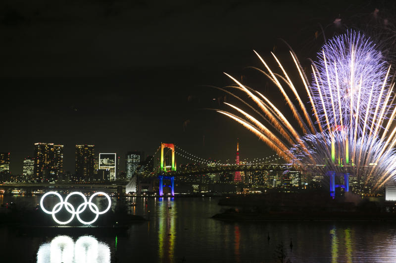 Fireworks explode near the illuminated Olympic rings during a ceremony held to celebrate the 6-months-to-go milestone for the Tokyo 2020 Olympics Friday, Jan. 24, 2020, in the Odaiba district of Tokyo. (AP Photo/Jae C. Hong)
