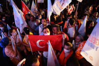 A supporter of the newly elected Turkish Cypriot leader Ersin Tatar holds a Turkish flag and celebrates with others in the Turkish occupied area in the north part of the divided capital Nicosia, Cyprus, Sunday, Oct. 18, 2020. Ersin Tatar, a hardliner who favors even closer ties with Turkey and a tougher stance with rival Greek Cypriots in peace talks has defeated the leftist incumbent in the Turkish Cypriot leadership runoff. (AP Photo/Nedim Enginsoy)