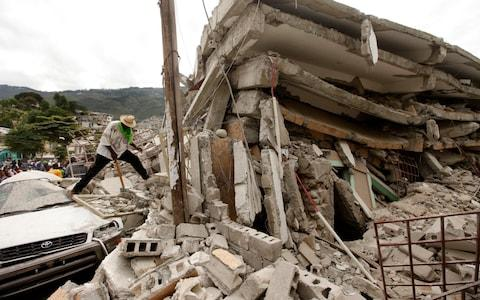 People work to free trapped victims from the rubble of a collapsed building after an earthquake in Port-au-Prince, Haiti. - Credit: AP