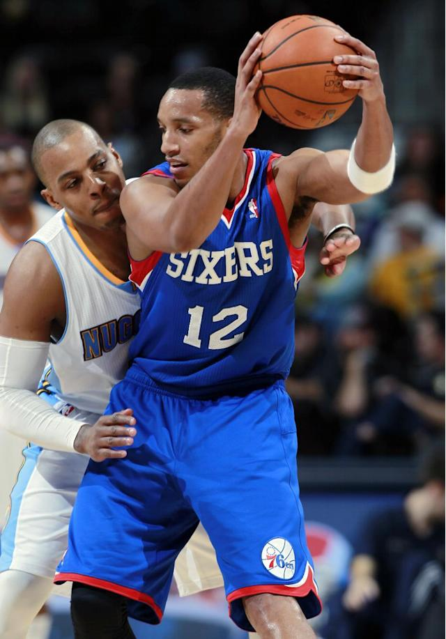 Philadelphia 76ers guard Evan Turner, front, looks to pass the ball as Denver Nuggets guard Randy Foye covers in the fourth quarter of the Sixers' 114-102 victory in an NBA basketball game in Denver on Wednesday, Jan. 1, 2014. (AP Photo/David Zalubowski)