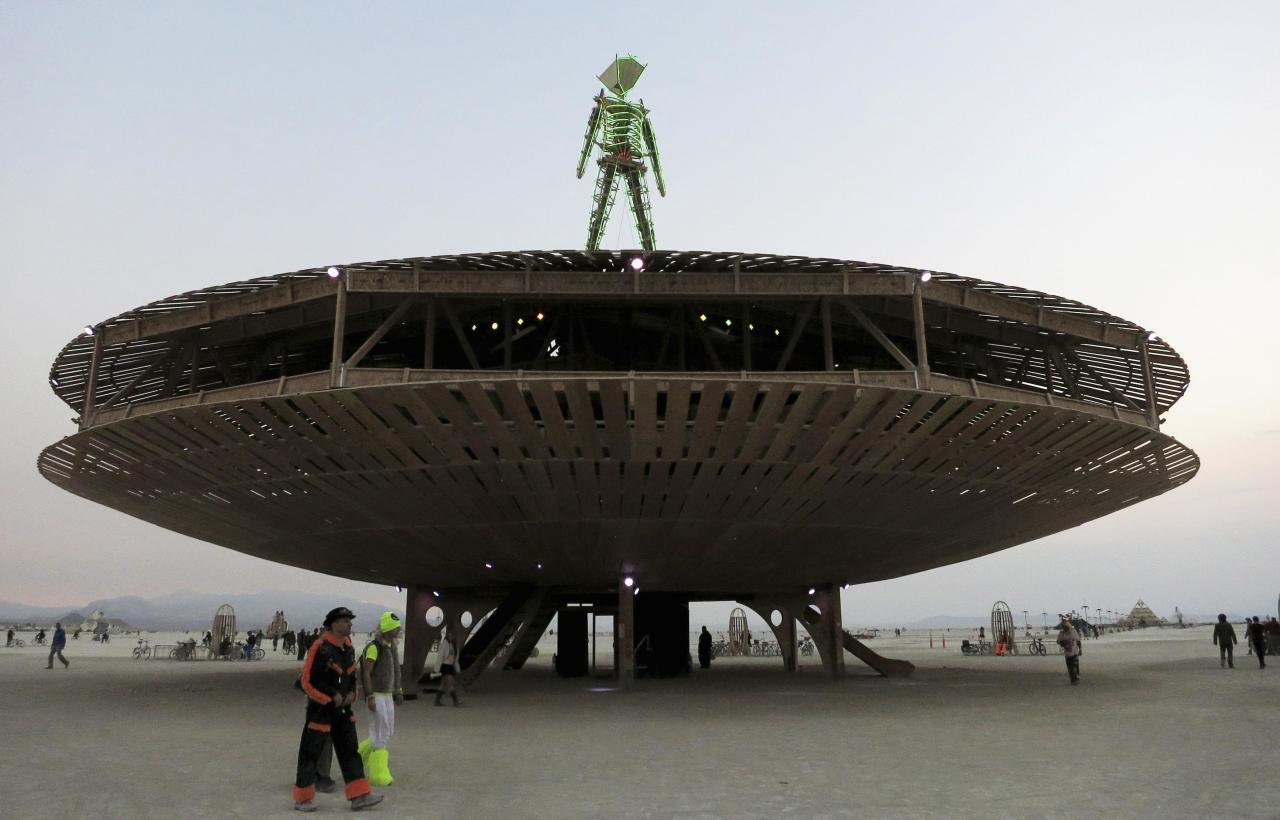 Participants walk past the effigy of the Man, seen at the center of the 2013 Burning Man arts and music festival in the Black Rock Desert of Nevada, August 29, 2013. The federal government issued a permit for 68,000 people from all over the world to gather at the sold out festival, which is celebrating its 27th year, to spend a week in the remote desert cut off from much of the outside world to experience art, music and the unique community that develops. REUTERS/Jim Bourg (UNITED STATES - Tags: SOCIETY) FOR USE WITH BURNING MAN RELATED REPORTING ONLY. FOR EDITORIAL USE ONLY. NOT FOR SALE FOR MARKETING OR ADVERTISING CAMPAIGNS. NO THIRD PARTY SALES. NOT FOR USE BY REUTERS THIRD PARTY DISTRIBUTORS