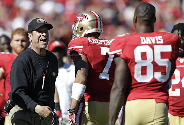 San Francisco 49ers head coach Jim Harbaugh, left, celebrates after quarterback Colin Kaepernick (7) and tight end Vernon Davis (85) connected for a 35-yard touchdown reception during the second quarter of an NFL football game against the Arizona Cardinals in San Francisco, Sunday, Oct. 13, 2013. (AP Photo/Marcio Jose Sanchez)