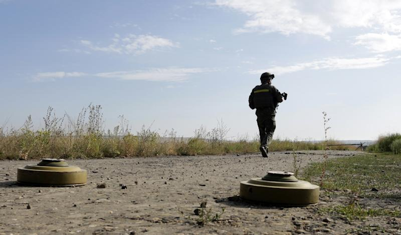 A Ukrainian soldier walks past anti-tank mines near the frontline in the Lugansk region, on August 27, 2015 (AFP Photo/Anatolii Stepanov)