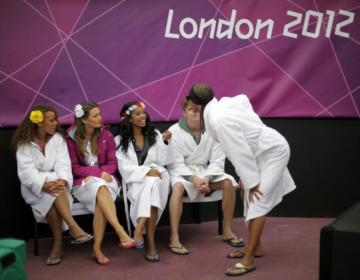 Dancers, wearing robes to keep themselves warm from the cold, wait outside the court before their performance at halftime at the London 2012 Olympic Games at Horse Guards Parade July 31, 2012.  REUTERS/Lucy Nicholson (BRITAIN  - Tags: SPORT OLYMPICS SPORT VOLLEYBALL ENVIRONMENT)