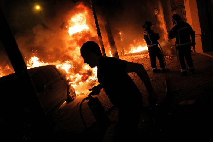 Firefighters and residents try to put out fires burning cars during clashes between protestors and police in Barcelona, Spain, Wednesday, Oct. 16, 2019. (Photo: Bernat Armangue/AP)