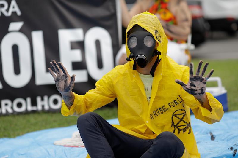 A demonstrator with his hands darkened with black paint and wearing a gas mask protests against the auction for the exploration of oil fields close to Abrolhos, a marine national park in Bahia state, in Rio de Janeiro, Brazil, Thursday, Oct. 10, 2019. Under pressure from environmental organizations, none of the 17 companies involved in the process presented any offers. (AP Photo/Silvia Izquierdo)