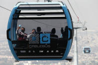Officials take pictures as they ride in a cable car between the Campos Revolucion and Tlalpexco stations, during the inauguration of a new aerial public transit system dubbed the Cablebus, in the Cuautepec neighborhood of northern Mexico City, Thursday, March 4, 2021. For the residents of Cuautepec, this new system, the first of four planned lines, will turn a commute to the nearest subway station, that can last up to two hours, into a 30-minute ride. (AP Photo/Rebecca Blackwell)