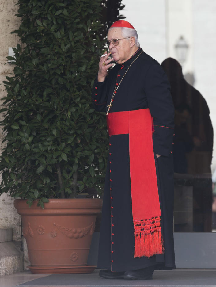 """Cardinal Jose' Policarpo smokes during a pause of the morning session of an extraordinary consistory in the Synod hall at the Vatican City, Friday, Feb. 21, 2014. Pope Francis is leading a two-day meeting urging his cardinals to find """"intelligent, courageous"""" ways to help families under threat today without delving into case-by-case options to get around Catholic doctrine. He said the church must find ways to help families with pastoral care that is """"full of love.""""(AP Photo/Alessandra Tarantino)"""