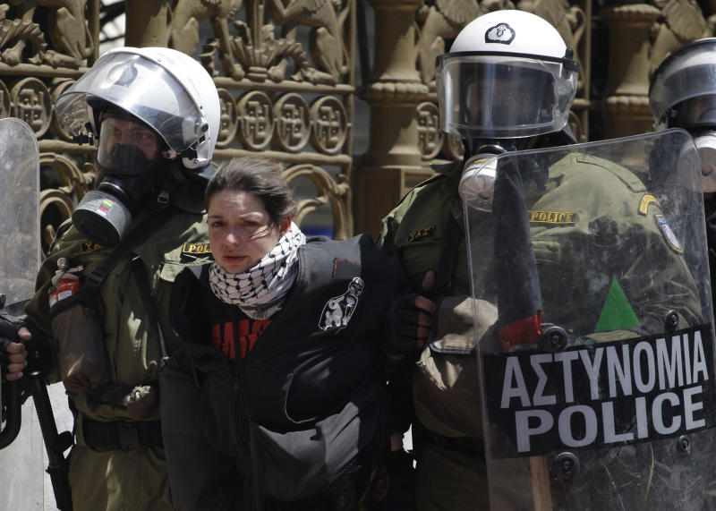 Riot police detain a protester during clashes in Athens, Wednesday, May 11, 2011. Riot police made heavy use of tear gas and stun grenades to disperse youths throwing stones and petrol bombs during a march attended by 20,000 people to protest the Greek government's harsh austerity measures.(AP Photo/ Petros Giannakouris)