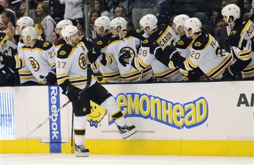 Boston Bruins center Patrice Bergeron (37) is congratulated by teammates after scoring a goal against the Los Angeles Kings in the second period of an NHL hockey game in Los Angeles, Saturday, March 24, 2012. (AP Photo/Lori Shepler)