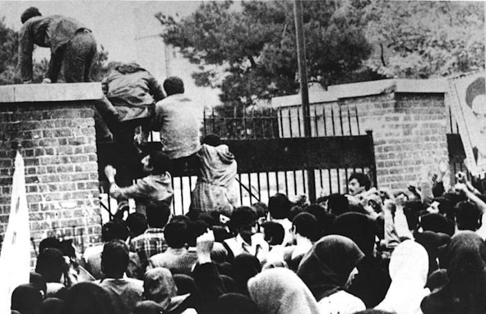 Iranian revolutionary students climb the American embassy's gate in Tehran on November 4, 1979 less than nine months after the toppling of the US-backed shah (AFP Photo/-)