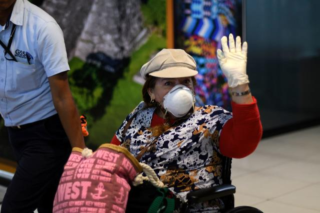 A passenger at La Aurora International Airport in Guatemala City is pictured waving while wearing a mask on 12 March. Waving is another 'safe' form of greeting. Guatemala has no confirmed cases. (Getty Images)