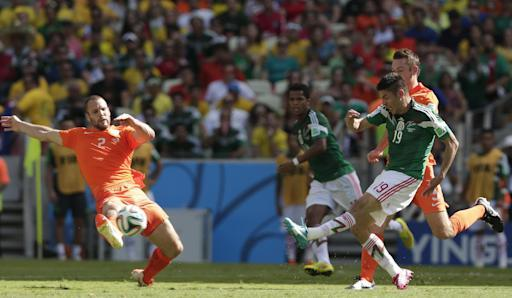 Netherlands' Ron Vlaar (2) stops a shot by Mexico's Oribe Peralta, right, during the World Cup round of 16 soccer match between the Netherlands and Mexico at the Arena Castelao in Fortaleza, Brazil, Sunday, June 29, 2014. (AP Photo/Marcio Jose Sanchez)