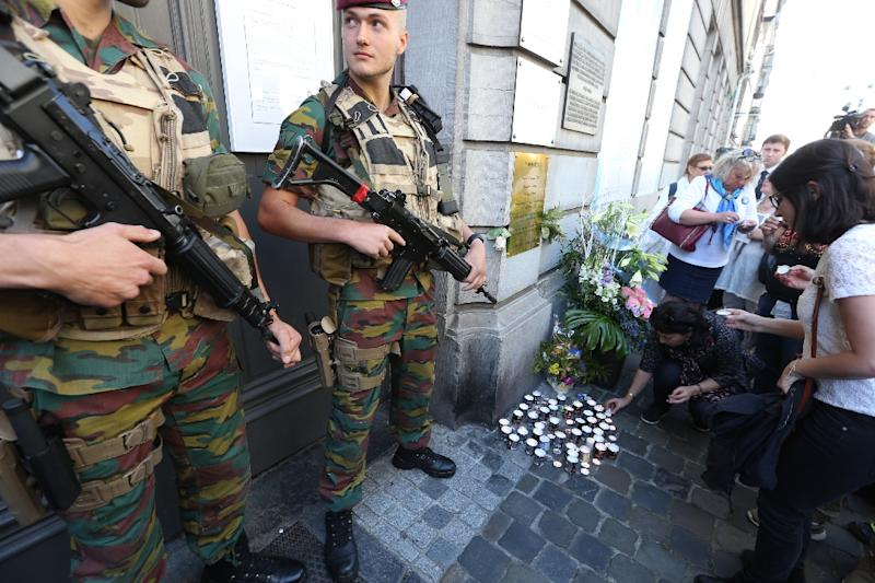 People lay down candles as soldiers stand guard at the entrance of the Jewish museum in Brussels, on May 24, 2015 (AFP Photo/Nicolas Maeterlinck)