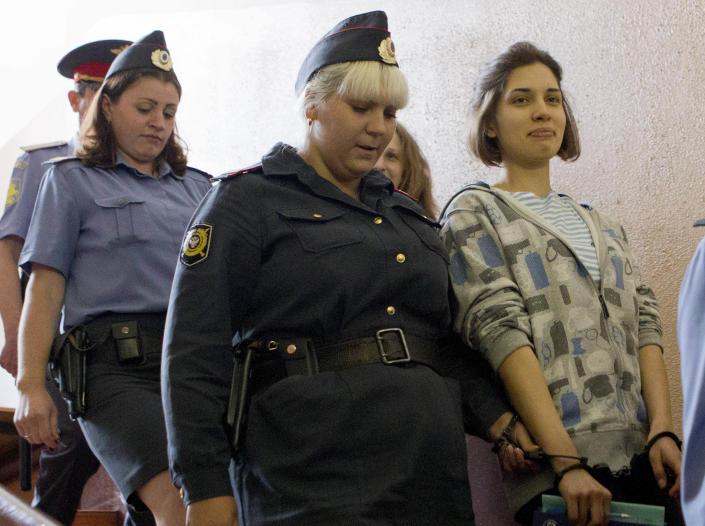 """Nadezhda Tolokonnikova, right, and Maria Alekhina, background center, members of feminist punk group Pussy Riot are excorted to a court room in Moscow, Russia, Friday, July 20, 2012. The trial of feminist punk rockers who chanted a """"punk prayer"""" against President Vladimir Putin from a pulpit inside Russia's largest cathedral started in Moscow on Friday amid controversy over the prank that divided devout believers, Kremlin critics and ordinary Russians. (AP Photo/Misha Japaridze)"""