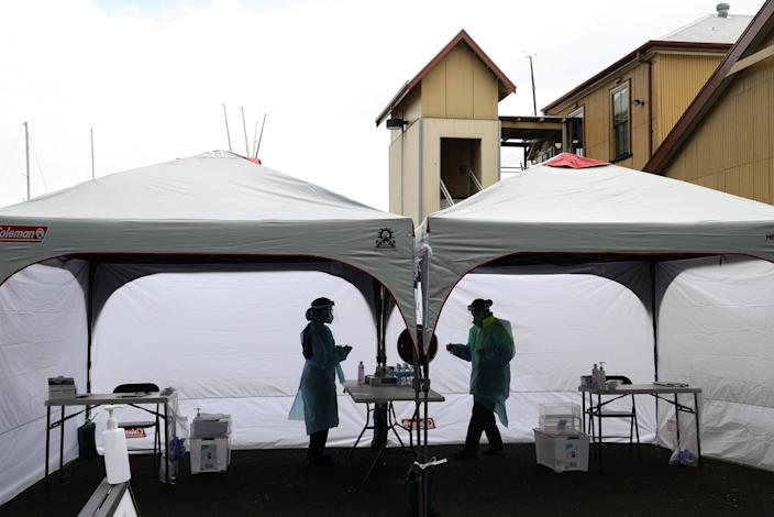 Image: Medical workers are seen at a COVID-19 pop-up testing centre in Sydney (Loren Elliott / Reuters)