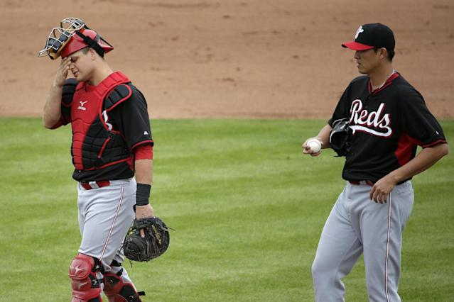 Cincinnati Reds catcher Devin Mesoraco, left, wipes his face after talking with pitcher Chien-Ming Wong, who gave up three runs to the San Francisco Giants during the fifth inning of a spring training baseball game in Scottsdale, Ariz., Thursday, March 6, 2014. (AP Photo/Chris Carlson)