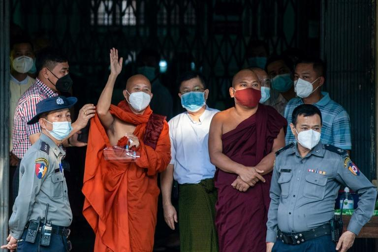 Ashin Wirathu waves to followers as he turns himself in at a Yangon police station