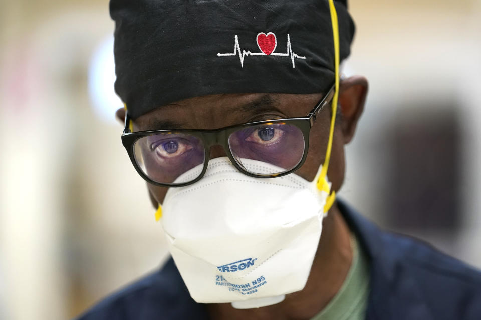 Dr. Tunji Ladipo, an emergency room physician at Roseland Community Hospital responds to a question Friday, Jan. 29, 2021, on the low rate of employees at the hospital who have not taken the COVID-19 vaccine at the South Side of Chicago. The resistance confounds Ladipo, who has seen the disease devastate countless patients and their families, and frequently works side by side with unvaccinated colleagues. ''Why people that work in the health-care field would not trust the science? I don't understand that,'' he said. (AP Photo/Charles Rex Arbogast)