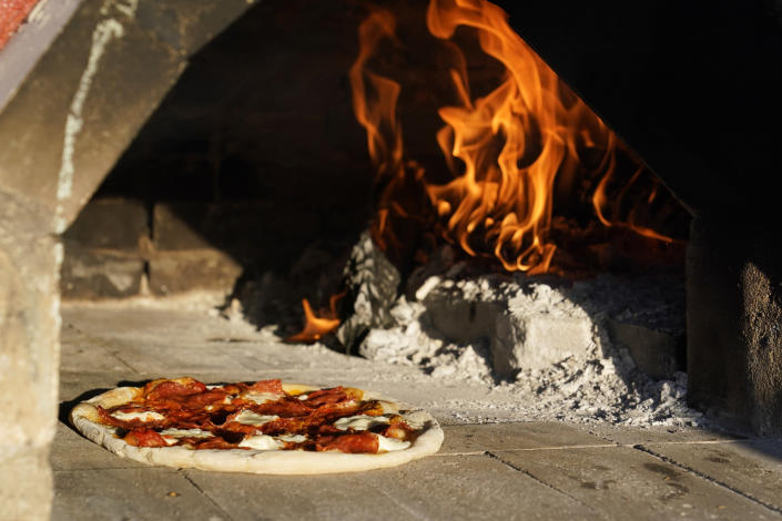 A pizza cooks in an outdoor pizza oven on April 3, 2021, in Scottsdale, Ariz. Beaten down by the pandemic, some laid-off or idle restaurant workers have pivoted to dishing out food from home. (AP Photo/Ross D. Franklin)