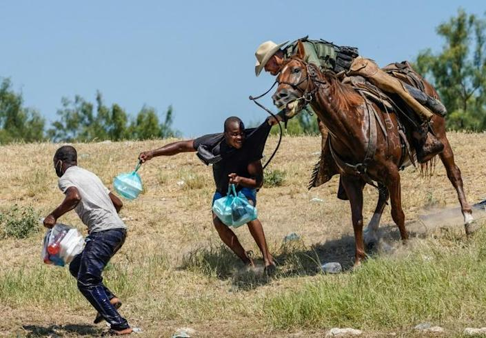 A US Border Patrol agent on horseback tries to stop a Haitian migrant from entering an encampment on the banks of the Rio Grande river on Sunday (AFP/PAUL RATJE)
