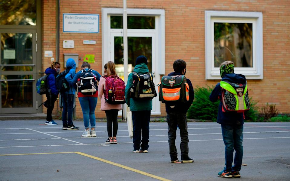 Children respect social distancing rules as they line up to enter the Petri primary school in Dortmund, western Germany, on May 7, 2020, as the school reopens for some pupils following lockdown due to the new coronavirus Covid-19 pandemic. - The primary schools in the western federal state of North Rhine-Westphalia reopened as planned for fourth-graders. (Photo by Ina FASSBENDER / AFP) (Photo by INA FASSBENDER/AFP via Getty Images) - INA FASSBENDER/AFP