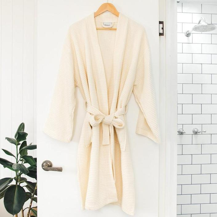 A waffle knit unisex robe made of a sustainable, organic and bamboo lyocell material hangs from a wooden hanger on the door of a bathroom. The bathroom has white subway tiles, a luxury shower head, and there is a lush potted rubber tree plant in the corner next to the door.