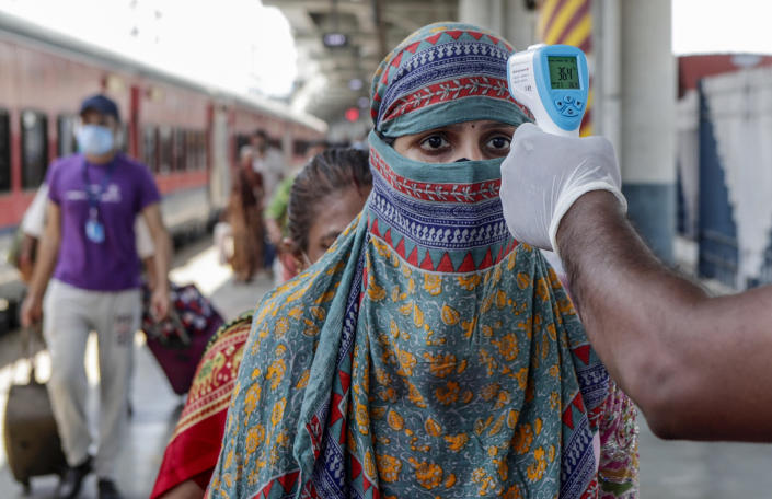 A health worker screening travelers to test for COVID-19 at train station in Mumbai, India, Monday, May 24,2020. India crossed another grim milestone Monday of more than 300,000 people lost to the coronavirus as a devastating surge of infections appeared to be easing in big cities but was swamping the poorer countryside. (AP Photo/Rajanish kakade)
