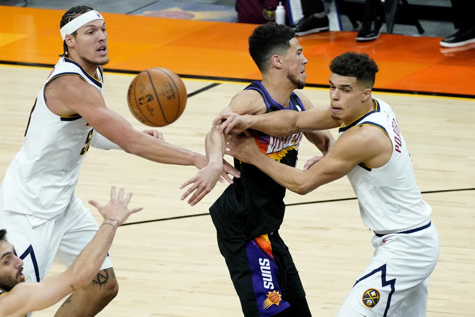 Phoenix Suns guard Devin Booker dishes off as Denver Nuggets forward Michael Porter Jr. , right, and Denver Nuggets forward Aaron Gordon, left, defend during the second half of Game 1 of an NBA basketball second-round playoff series, Monday, June 7, 2021, in Phoenix. (AP Photo/Matt York)