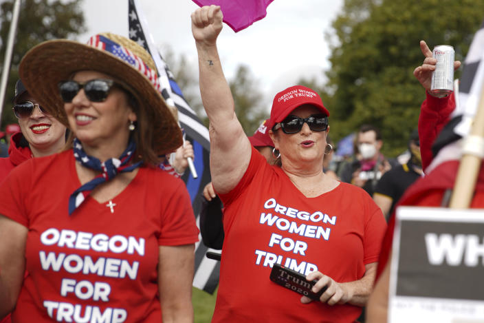 Women cheer as members of the Proud Boys and other right-wing demonstrators rally on Saturday, Sept. 26, 2020, in Portland, Ore. (AP Photo/Allison Dinner)