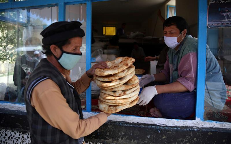 A man receives free bread from the municipality during a lockdown aimed at curbing the spread of the coronavirus, in the holy fasting month of Ramadan in Kabul, Afghanistan