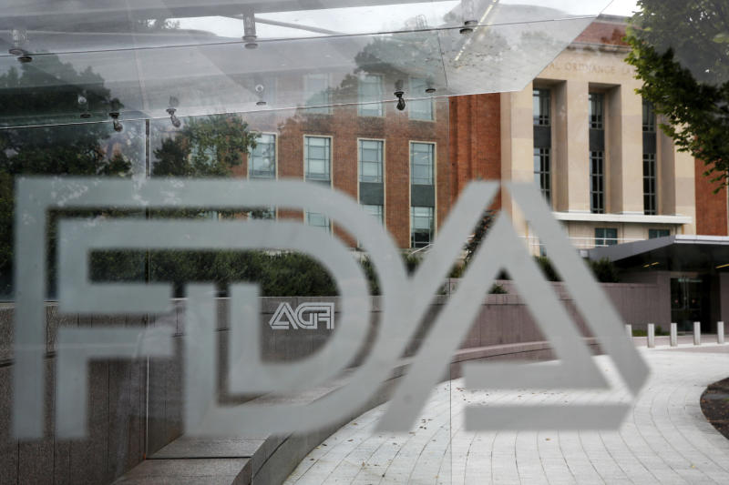 FILE - This Aug. 2, 2018, file photo shows the U.S. Food and Drug Administration building behind FDA logos at a bus stop on the agency's campus in Silver Spring, Md. On Thursday, Dec. 12, 2019, U.S. health regulators said they approved the drug Vyondys 53 for a debilitating form of muscular dystrophy, a surprise decision after the medication was rejected for safety concerns just four months earlier. (AP Photo/Jacquelyn Martin, File)