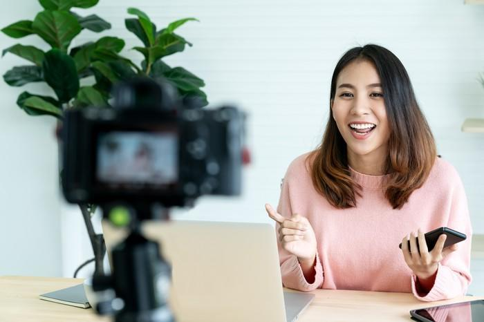 Young asian woman smiles and speaks into a mounted camera taking a video of her behind a desk.
