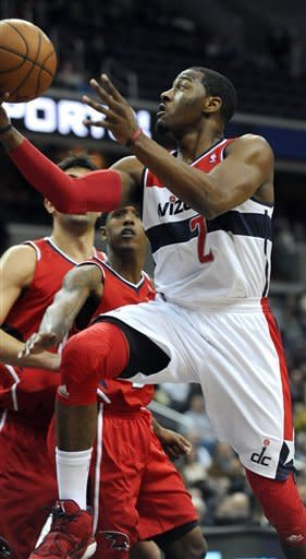 Washington Wizards guard John Wall (2) drives to the basket away from Atlanta Hawks guard Louis Williams during the first half of their NBA basketball game on Saturday, Jan. 12, 2013, in Washington. Wall had been sidelined since being diagnosed with a stress injury to his left kneecap in September. (AP Photo/Richard Lipski)