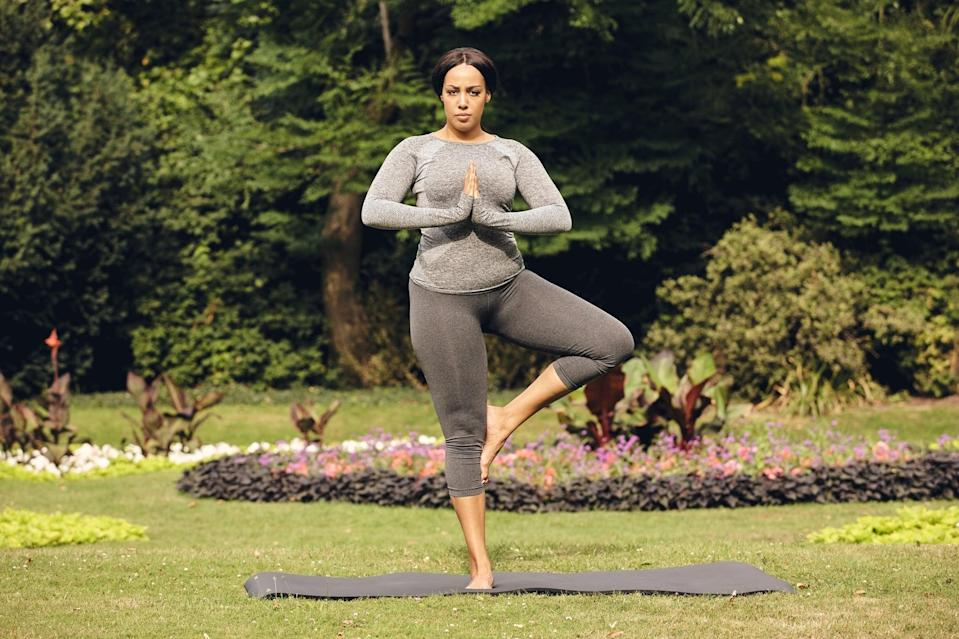 Full length portrait of healthy woman practicing yoga in the park. Fitness woman doing tree pose yoga.