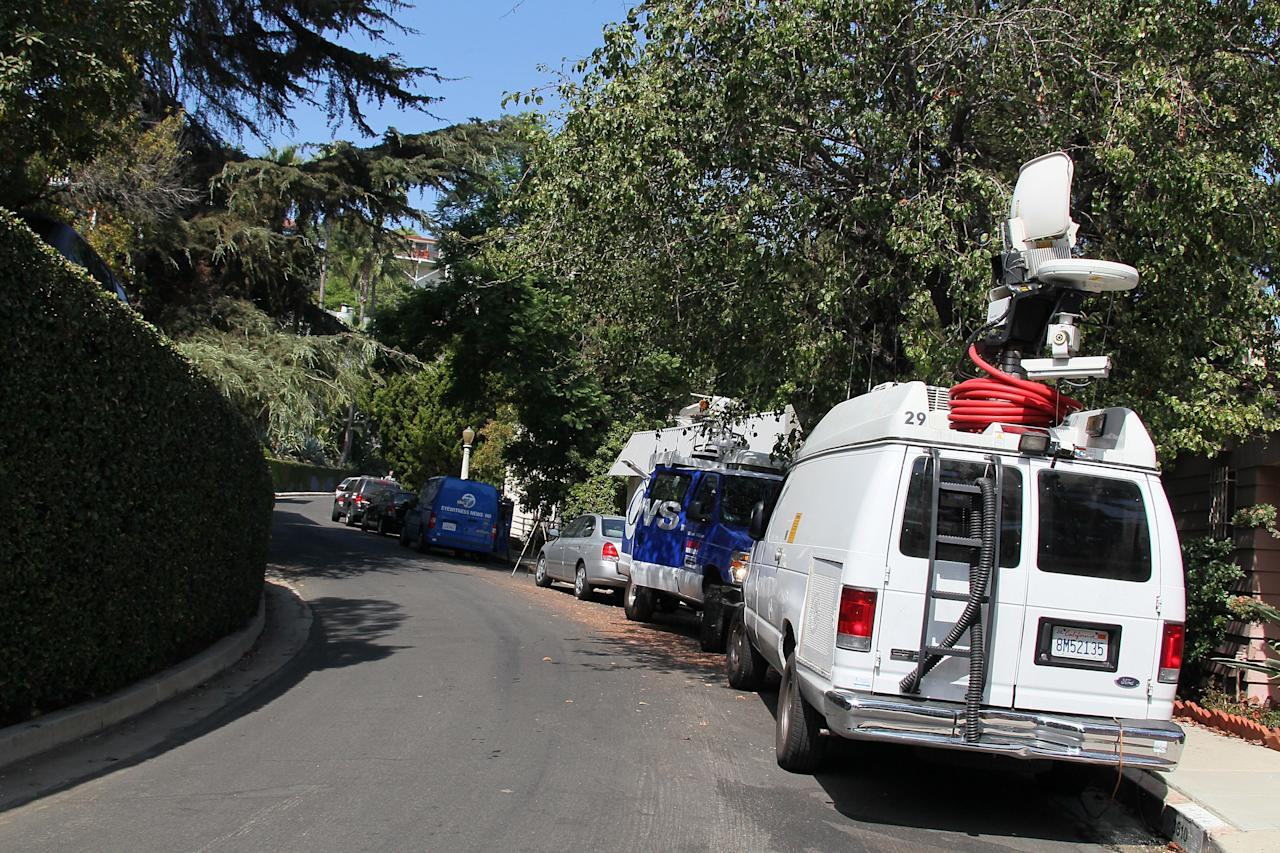 LOS ANGELES, CA - SEPTEMBER 27:  News vans are seen at the building (L) where actor Johnny Lewis was found dead on September 27, 2012 in Los Angeles, California.  Lewis was found dead September 26, 2012 after apparently falling from the roof of the building he lived in.  He is also a suspect in the death of a woman who is thought to have been his landlord and was found dead inside the house.  (Photo by David Livingston/Getty Images)