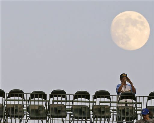 A full moon rises over a fan taking a photograph of a baseball game between the Milwaukee Brewers and Houston Astros Tuesday, July 31, 2012, in Milwaukee. (AP Photo/Jeffrey Phelps)