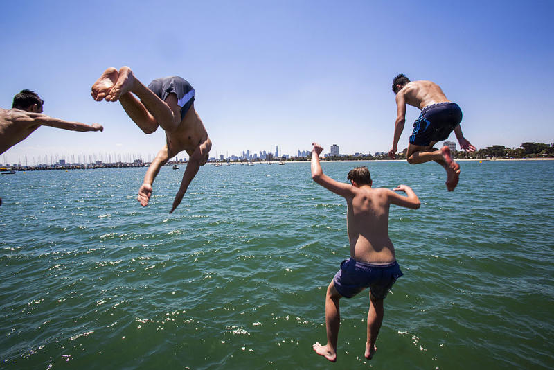 A group of boys are seen jumping into the ocean. Source: Getty
