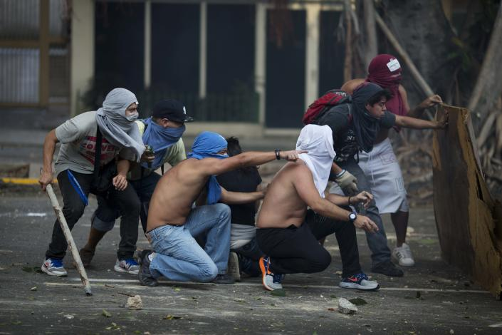 Anti-government protesters take cover during clashes with riot police in Caracas, Venezuela, Saturday, Feb. 22, 2014. After their opposition rally broke up in the late afternoon, in a pattern that has been seen in past demonstrations about 1,000 stragglers erected barricades of trash and other debris and threw rocks and bottles at police and National Guardsmen. The troops responded with volleys of tear gas to prevent the students from reaching a highway and blocking traffic. (AP Photo/Rodrigo Abd)