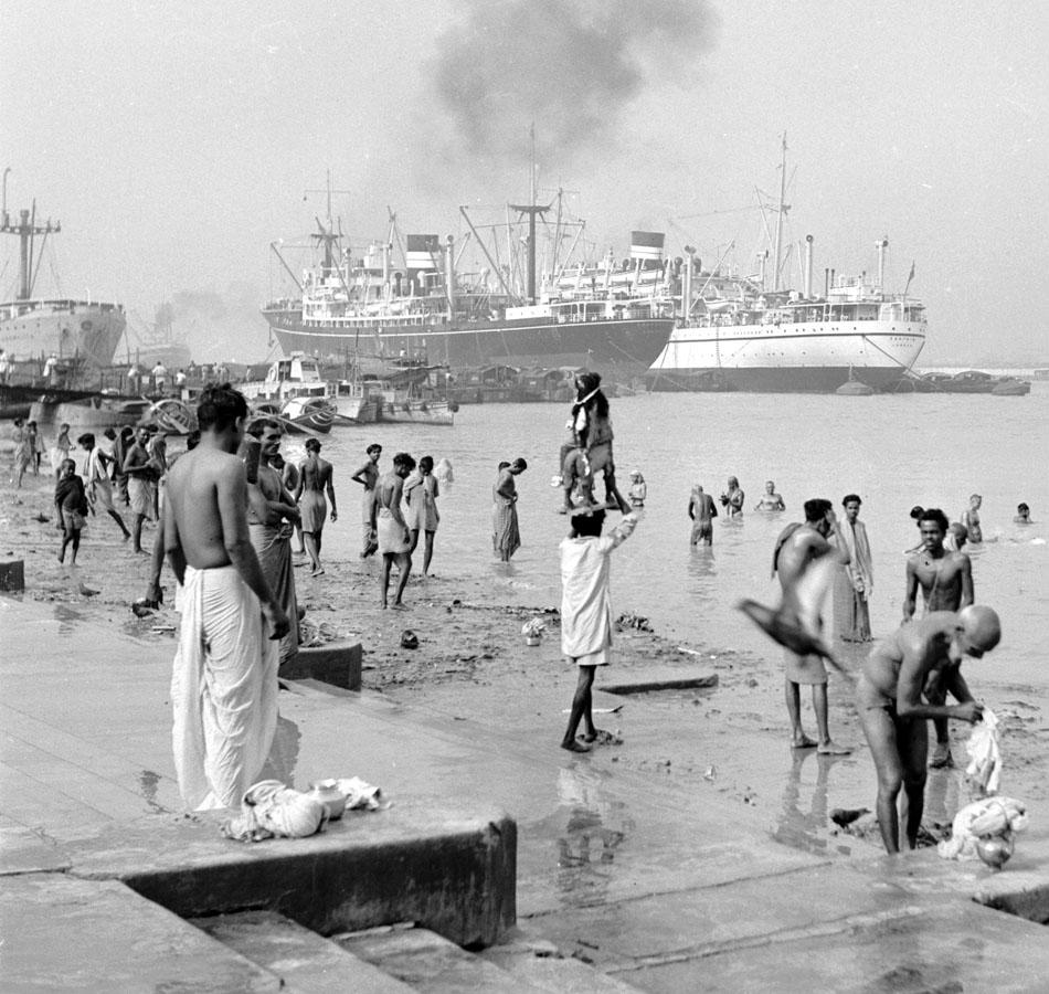 circa 1950:  Men having an early morning wash in Calcutta's busy Hooghly river, with its large freighters in the background.  (Photo by Three Lions/Getty Images)
