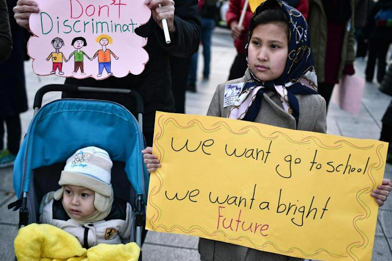 Delayed: A child refugee carries a sign during a demonstration (AFP/Getty Images)