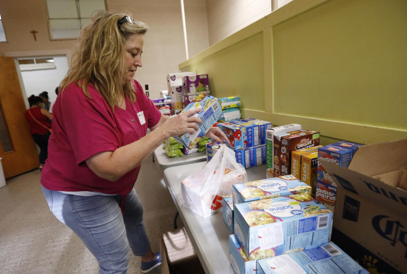 St. Joseph Catholic Church parishioner Gayle Price of Madison, stacks boxes of crackers in a storage room at the old school formerly used by Sacred Heart Catholic Church, Friday, Aug. 9. 2019 in Canton, Miss. Rice, beans, canned meats, diapers and other sundry items are being collected to assist families affected by the immigration raids of several food processing plants, including one in Canton. (AP Photo/Rogelio V. Solis)