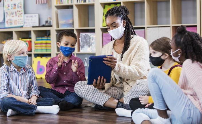 """<span class=""""caption"""">Teachers have faced high levels of stress and burnout throughout the pandemic.</span> <span class=""""attribution""""><a class=""""link rapid-noclick-resp"""" href=""""https://www.gettyimages.com/detail/photo/preschool-teacher-students-in-class-wearing-masks-royalty-free-image/1294218659"""" rel=""""nofollow noopener"""" target=""""_blank"""" data-ylk=""""slk:Kali9/E+ Collection via Getty Images"""">Kali9/E+ Collection via Getty Images</a></span>"""