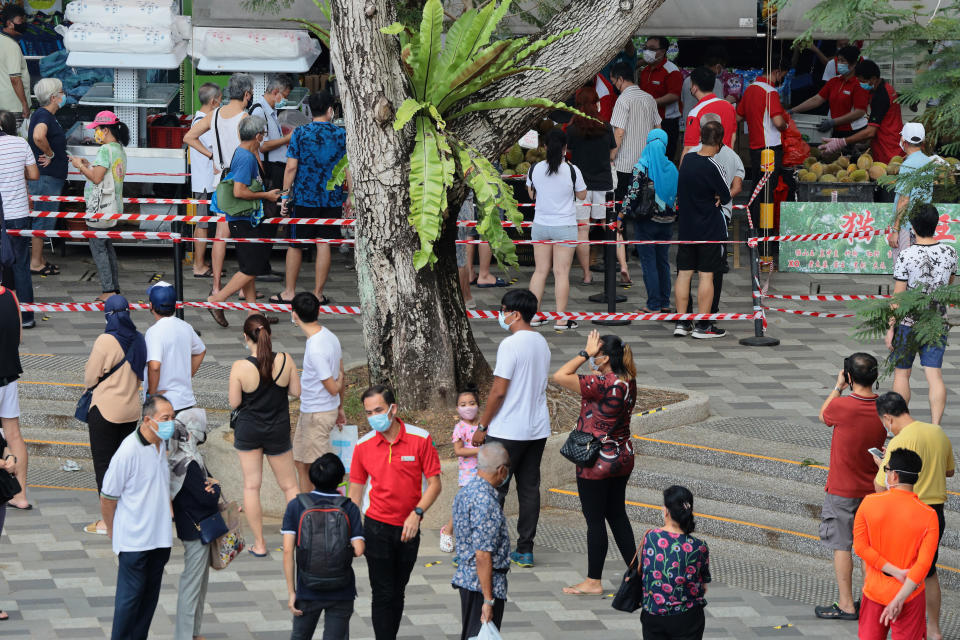 People wait in queue to buy durian on June 24, 2021 in Singapore. On June 21, Singapore entered into a calibrated easing of social management measures as local community COVID-19 cases remain under control. (Photo by Suhaimi Abdullah/NurPhoto via Getty Images)