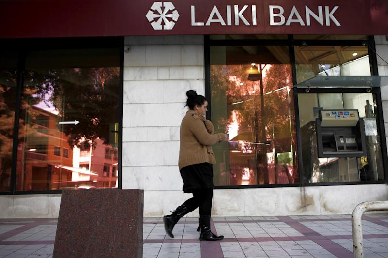 "A woman walks outside of Laiki Bank capital Nicosia, Cyprus, Wednesday, March 13, 2013. Cyprus' president Nicos Anastasiades says talks with international creditors for a much-needed rescue loan to keep the country from going bankrupt are paying off.  Anastasiades urged patience, saying that it will soon become clear that ""hard work produces good results."" (AP Photo/Petros Karadjias)"