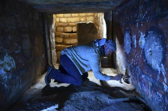 An archeologist brushes off dust at a burial chamber at the archeological site of Atzompa, in the Mexican state of Oaxaca in this undated handout photo released by the National Institute of Anthropology and History (INAH) on July 18, 2012.