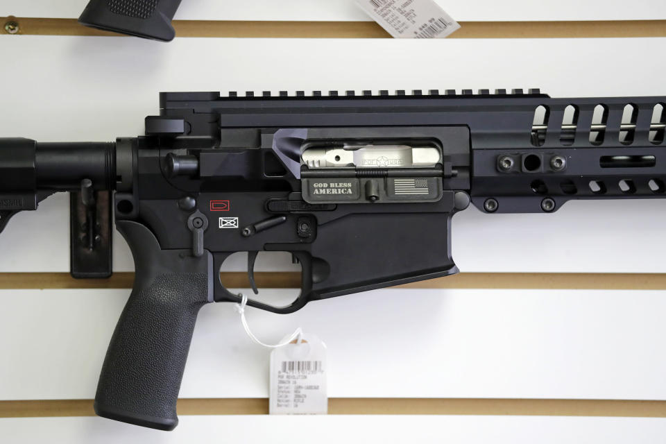"""FILE - In this photo taken Oct. 2, 2018, a semi-automatic rifle, with """"God Bless America"""" imprinted on it, is displayed for sale on the wall of a gun shop in Lynnwood, Wash. A dozen county sheriffs in Washington state are refusing to enforce restrictions on semi-automatic rifles that voters approved in November. They say the new law might be unconstitutional, and they're waiting for the courts to weigh in. (AP Photo/Elaine Thompson, File)"""