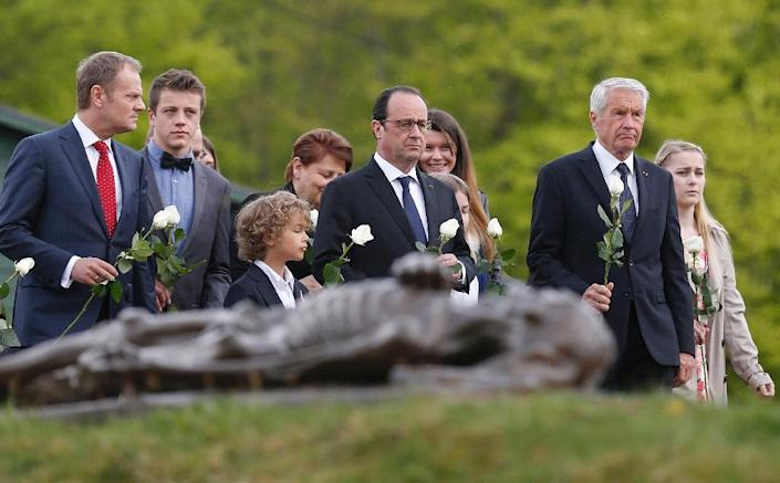 President Francois Hollande (C), European Council President Donald Tusk (L) and Secretary-General of the Council of Europe Thorbjorn Jagland (R) hold white roses to be placed at the grave of ashes in the Natzwiller-Struthof concentration camp (AFP Photo/Vincent Kessler)