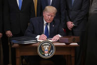 President Donald Trump signs a U.S. China trade agreement during an event with Chinese Vice Premier Liu He, in the East Room of the White House, Wednesday, Jan. 15, 2020, in Washington. (AP Photo/ Evan Vucci)