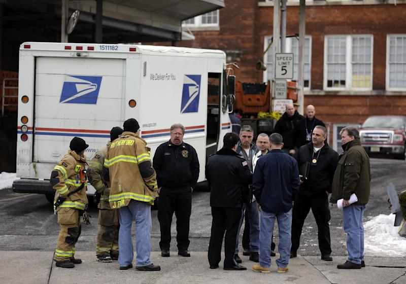 Law enforcement and other personnel gather Friday, Jan. 31, 2014, outside a post office in Rutherford, N.J. White powder was mailed to businesses near the site of Sunday's Super Bowl, prompting an investigation by the FBI and other law enforcement. A federal law enforcement official said one of the envelopes contained baking soda. (AP Photo/Jeff Roberson)